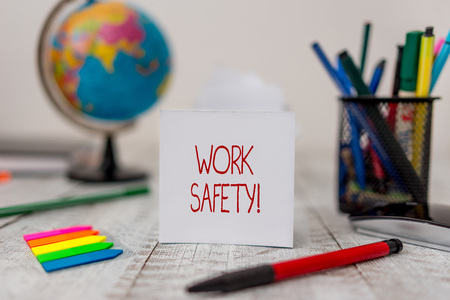 Text sign showing Work Safety. Business photo text policies and procedures in place to ensure health of employees Stationary and paper sheets plus small arrows with globe on the wooden desk Stock Photo