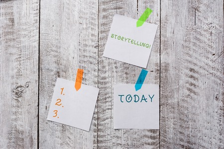 Conceptual hand writing showing Storytelling. Concept meaning activity writing stories for publishing them to public Plentiful of plain paper sheet attached with wooden textured table Stock Photo