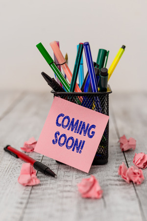 Writing note showing Coming Soon. Business concept for event or action that will happen after really short time Writing equipment and paper scraps with blank sheets on the wooden desk