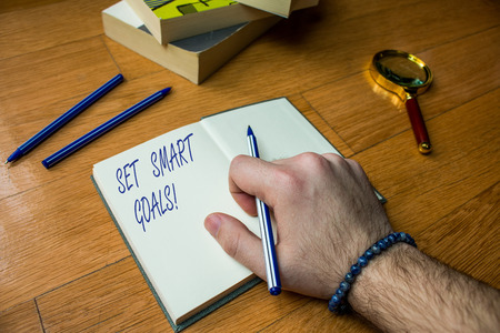 Word writing text Set Smart Goals. Business photo showcasing list to clarify your ideas focus efforts use time wisely Close up view man writing notebook pen set lying wooden table two books