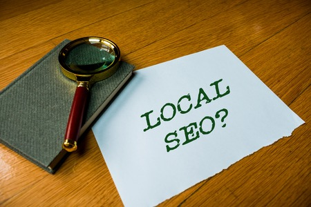 Text sign showing Local Seo question. Business photo text incredibly effective way to market your local business online Close up electronic device gadget magnifying glass resting wooden table