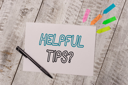 Handwriting text Helpful Tips Question. Conceptual photo secret information or advice given to be helpful knowledge Plain note paper and line arrow stickers with pen above the wooden table