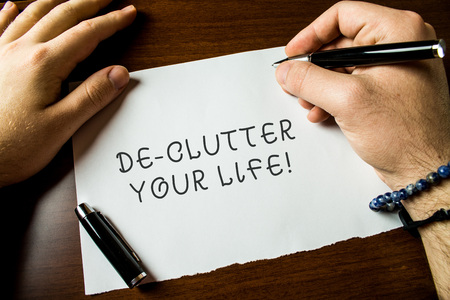Text sign showing De Clutter Your Life. Business photo text remove unnecessary items from untidy or overcrowded places Close up view male hands writing blank stationary paper pens wooden table
