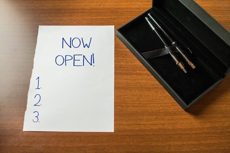 Conceptual hand writing showing Now Open. Concept meaning leave door or windows not closed or barred at this current time Top view stationary lying wooden table case ball point set