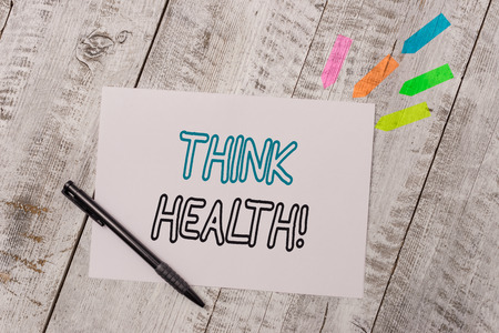 Handwriting text Think Health. Conceptual photo state of complete physical mental and social well being Plain note paper and line arrow stickers with pen above the wooden table Foto de archivo