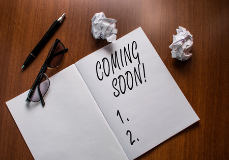 Conceptual hand writing showing Coming Soon. Concept meaning event or action that will happen after really short time Notebook small wrinkled paper balls reading glasses wooden table