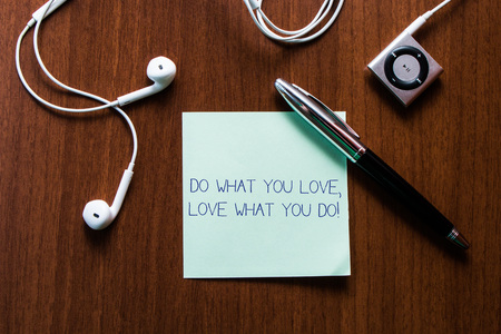 Handwriting text writing Do What You Love Love What You Do. Conceptual photo you able doing stuff you enjoy it to work in better places then Upper view earphones music device and stick pad lying wooden timber table Stockfoto