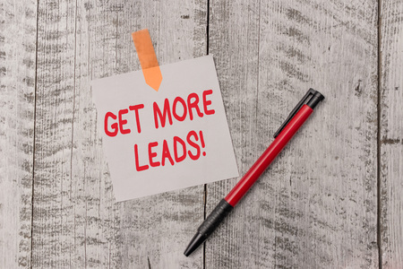 Text sign showing Get More Leads. Business photo text initiation consumer interest or enquiry products or services One plain blank paper sheet and a pen attached with wooden textured table