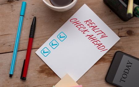 Writing note showing Reality Check Ahead. Business concept for makes them recognize truth about situations or difficulties Wooden table stationary tablet coffee cup New project challenges