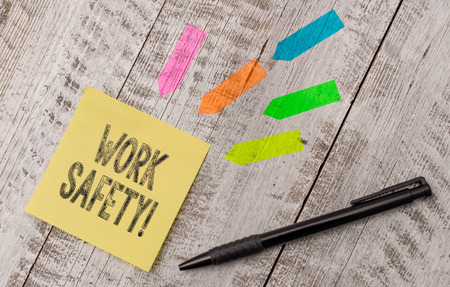 Writing note showing Work Safety. Business concept for policies and procedures in place to ensure health of employees Note paper and line arrow stickers on the top of wooden table desk