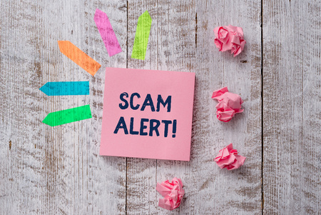 Handwriting text writing Scam Alert. Conceptual photo fraudulently obtain money from victim by persuading him Plain note paper and line arrow stickers on the top of wooden table desk Stock Photo