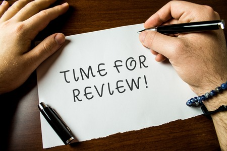 Text sign showing Time For Review. Business photo text formal assessment of something with intention instituting change Close up view male hands writing blank stationary paper pens wooden table