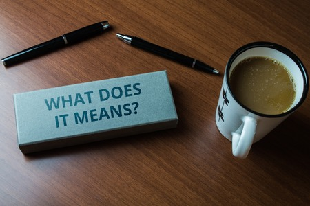 Word writing text What Does It Means question. Business photo showcasing asking meaning something said and do not understand Upper close view two ball point pens case set coffee cup lying wooden table