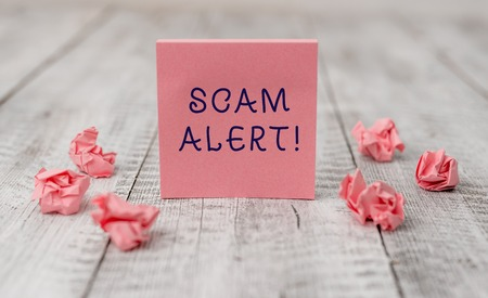 Handwriting text writing Scam Alert. Conceptual photo fraudulently obtain money from victim by persuading him Thick set of plain note paper with scraps on the wooden textured table Stock Photo