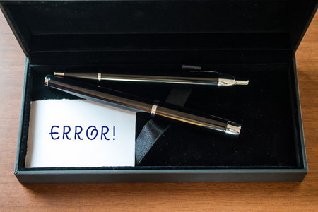 Writing note showing Error. Business concept for state or condition of being wrong in conduct judgement or program Close up case ball point fountain pens set blank card lying on wooden