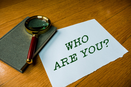 Text sign showing Who Are You question. Business photo text asking demonstrating identity or demonstratingal information Close up electronic device gadget magnifying glass resting wooden table