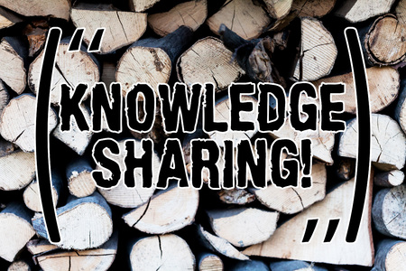 Handwriting text Knowledge Sharing. Conceptual photo deliberate exchange of information that helps with agility Background dry chopped firewood logs stacked up in a pile winter chimney