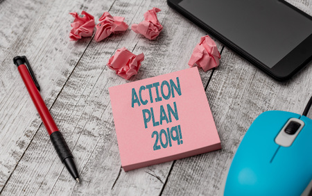 Text sign showing Action Plan 2019. Business photo showcasing proposed strategy or course of actions for current year Writing equipment and paper plus scraps with gadgets on the wooden desk