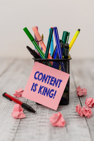 Writing note showing Content Is King. Business concept for marketing focused growing visibility non paid search results Writing equipment and paper scraps with blank sheets on the wooden desk