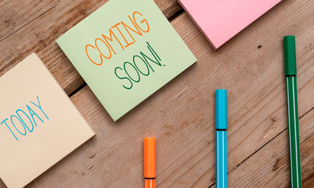 Text sign showing Coming Soon. Business photo showcasing event or action that will happen after really short time Note papers and stationary placed sideways on top of softhued backdrop