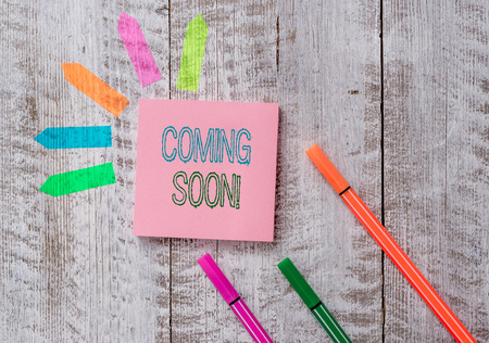 Text sign showing Coming Soon. Business photo text event or action that will happen after really short time Plain note paper and line arrow stickers on the top of wooden table desk