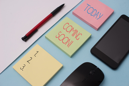 Writing note showing Coming Soon. Business concept for event or action that will happen after really short time Note papers and stationary plus gadgets placed sideways above backdrop