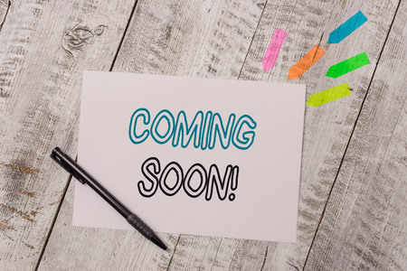 Handwriting text Coming Soon. Conceptual photo event or action that will happen after really short time Plain note paper and line arrow stickers with pen above the wooden table
