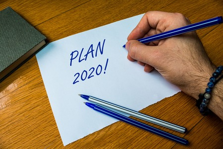 Handwriting text writing Plan 2020. Conceptual photo detailed proposal doing achieving something next year Top vie male handwriting wooden desk electronic device Writing down project