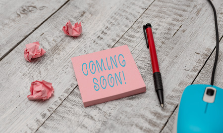 Text sign showing Coming Soon. Business photo showcasing event or action that will happen after really short time Writing equipment and computer mouse with paper sheets on the wooden desk Imagens