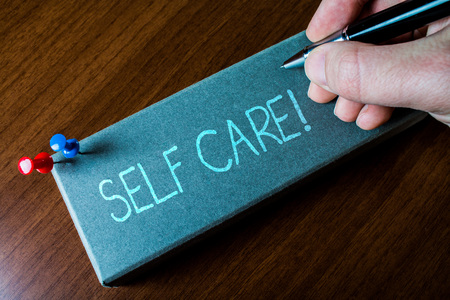 Writing note showing Self Care. Business concept for practice of taking action to preserve or improve ones own health Close up left man right hand holding pen fixed pins lying wooden table