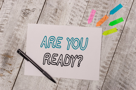 Handwriting text Are You Ready Question. Conceptual photo used telling someone start something when feel prepared Plain note paper and line arrow stickers with pen above the wooden table Stock Photo