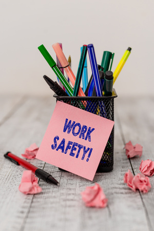 Writing note showing Work Safety. Business concept for policies and procedures in place to ensure health of employees Writing equipment and paper scraps with blank sheets on the wooden desk
