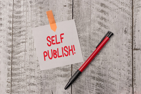 Text sign showing Self Publish. Business photo text writer publish piece of ones work independently at own expense One plain blank paper sheet and a pen attached with wooden textured table
