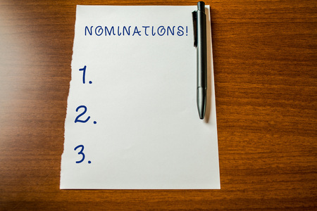 Handwriting text Nominations. Conceptual photo action of nominating or state being nominated for prize Upper view blank stationary paper lying wooden table pen. Writing essay