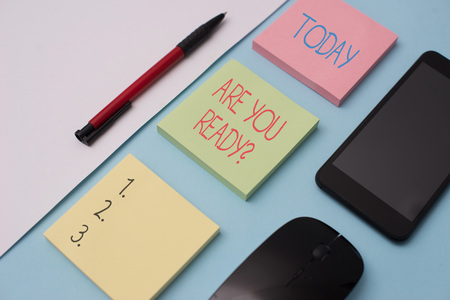 Writing note showing Are You Ready Question. Business concept for used telling someone start something when feel prepared Note papers and stationary plus gadgets placed sideways above backdrop