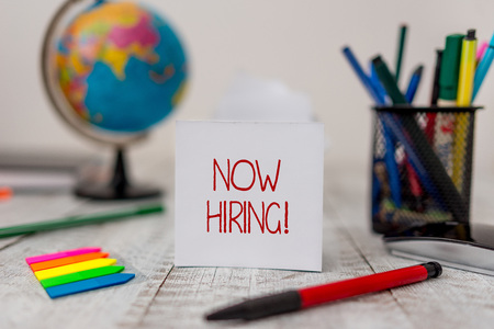 Text sign showing Now Hiring. Business photo text finding evaluating working relationship with future employees Stationary and paper sheets plus small arrows with globe on the wooden desk