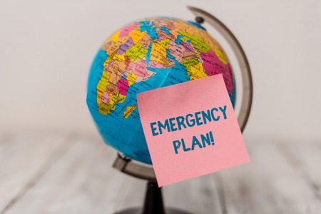 Word writing text Emergency Plan. Business photo showcasing actions developed to mitigate damage of potential events Plain note paper sticked to a mini miniature of the world on the wooden table Stock Photo