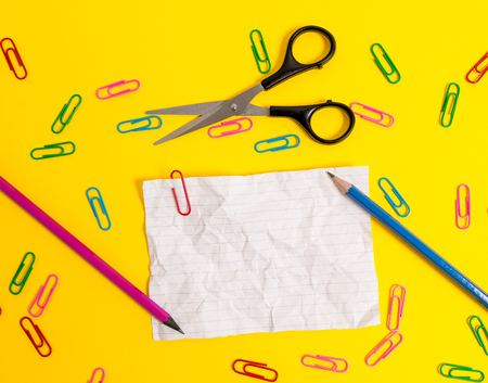 Crushed striped paper sheet scissors pencils clips colored background 免版税图像