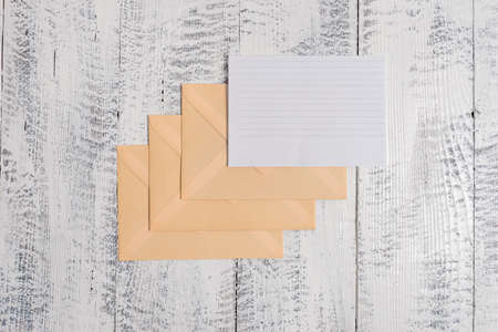 Three envelopes around ruled paper sheet old wooden vintage background Banque d'images
