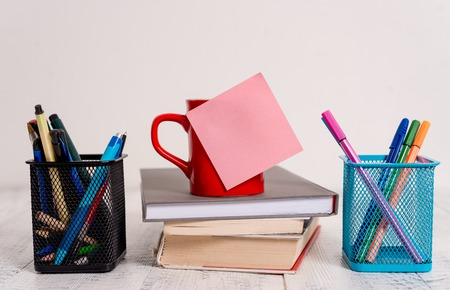 Coffee cup blank sticky note stacked books pen metal holders wooden table