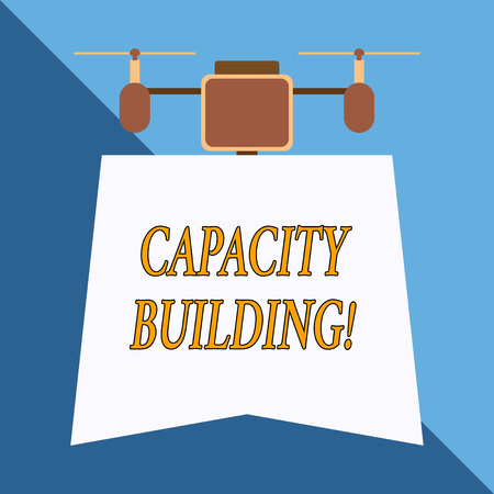 Writing note showing Capacity Building. Business concept for Strengthen the abilities of individuals Workforce planning Drone holding downwards banner. Geometrical abstract background design Stockfoto