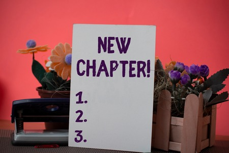 Text sign showing New Chapter. Business photo showcasing Starting ultimately something goals created in your mind Flowers and writing equipments plus plain sheet above textured backdrop Stok Fotoğraf