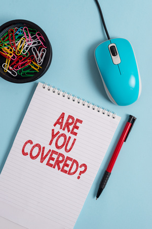 Text sign showing Are You Covered Question. Business photo text asking showing if they had insurance in work or life Notebook and writing equipment with computer mouse above pastel backdrop 写真素材