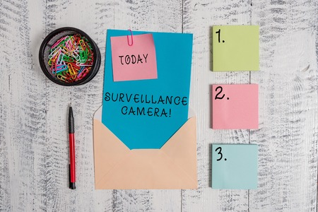 Writing note showing Surveillance Camera. Business concept for Closed Circuit Television transmit signal on monitors Envelope letter sticky note ballpoint clips on wooden background