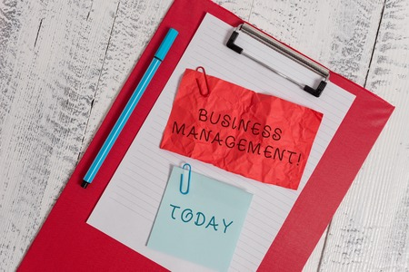 Writing note showing Business Management. Business concept for Overseeing Supervising Coordinating Business Operations Clipboard paper sheet crushed sticky note clip marker wooden background Foto de archivo