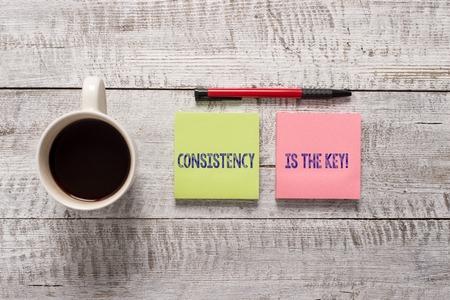 Signo de texto que muestra la consistencia es la clave. Foto y texto de negocios rompiendo los malos hábitos y formando los buenos estacionario colocado junto a una taza de café negro sobre la mesa de madera Foto de archivo