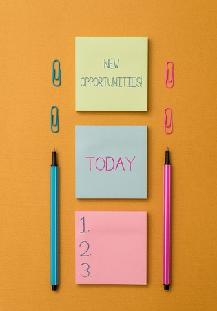 Word writing text New Opportunities. Business photo showcasing exchange views condition favorable for attainment goal Front view blank colored sticky note two ballpoints clips yolk background
