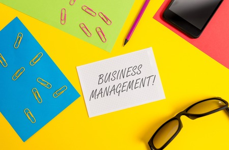 Text sign showing Business Management. Business photo text Overseeing Supervising Coordinating Business Operations Paper sheets pencil clips smartphone eyeglasses notebook color background