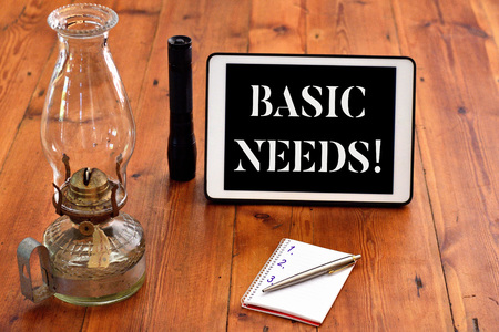 Word writing text Basic Needs. Business photo showcasing measurement of absolute poverty in developing countries Writing equipments placed next to gadget plus a classic vintage lantern Stock Photo