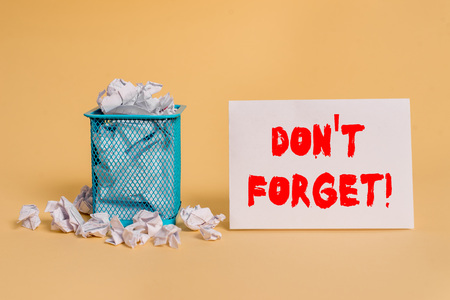 Handwriting text Don T Forget. Conceptual photo remind someone important fact or detail they should consider crumpled paper trash and stationary with empty paper placed in trash can Stock Photo